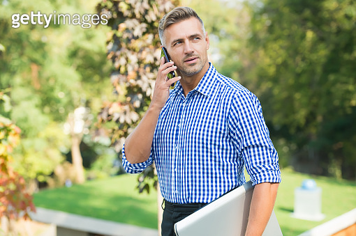 the day starts with talk. handsome guy carry laptop. male has conversation. communication in modern life. agile business. mature unshaven man shirt. male speaking on mobile phone outdoor