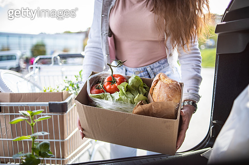 A beautiful young woman finished shopping in a supermarket, bought vegetables and beautiful flowers.