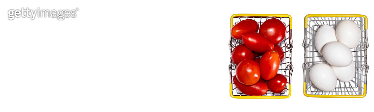 Ripe red tomatoes in shopping basket next to basket full of fresh white eggs. Isolated on white background. Eggs and tomatoes trading and shopping concepts. Banner size. Copy space