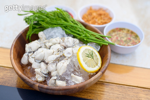 Fresh oysters served in a plate with thai spicy seafood sauce