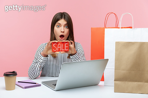 Shocked excited woman office worker holding and showing sale card looking with astonishment, sitting at workplace with laptop and doing shopping online