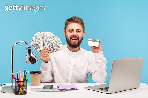 Happy smiling man office worker holding and showing dollar cash and credit card sitting at workplace with laptop, bank transaction, crediting