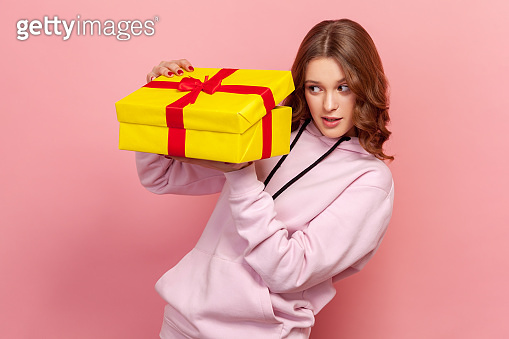Portrait of curious teenager girl with brunette hair in hoodie secretly peeping inside wrapped yellow gift box, birthday present