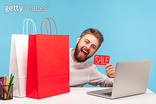 Happy cheerful man office worker looking behind paper shopping bags and smiling holding sale card, enjoying low prices during shopping