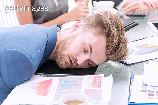 Businessman wear blue suit with white coffee sleeping at white office desk breakdown looking tired. Business people working overtime headache.