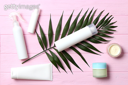 Set of cosmetic jars of white color and palm branches on a colored background