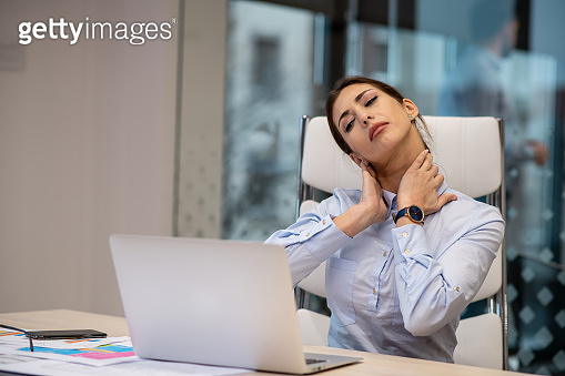 Young woman having neck pain. She is in her office, sitting in front of laptop.