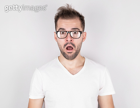 Surprised man with tousled hair wearing glasses in white t-shirt on gray background
