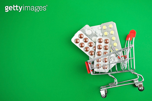 capsules,pills,medicines in blisters on green background in shopping cart. Pharmacy,people and health concept.Online ordering of medicines,online shopping.Vitamins and dietary supplements.Copy space.