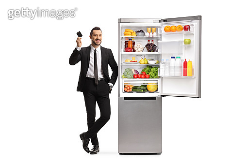 Full length portrait of a businessman holding a credit card and leaning on a fridge