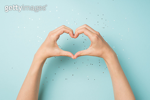 First person top view photo of female hands making heart with fingers on isolated pastel blue background with copyspace