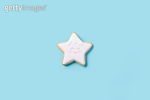 Cookies in the form of a star with icing painted a face on a blue background. Top view, flat lay.
