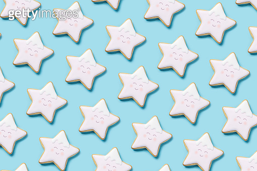 Background with cookies in the form of a star from above with icing on a blue background. Top view, flat lay