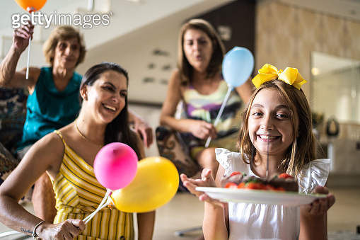 Girl celebrating her birtday party with family at home and doing a video call