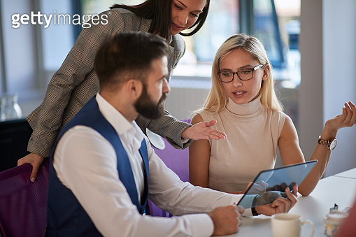 young business man showing something on tablet to coworkers . business communication concept