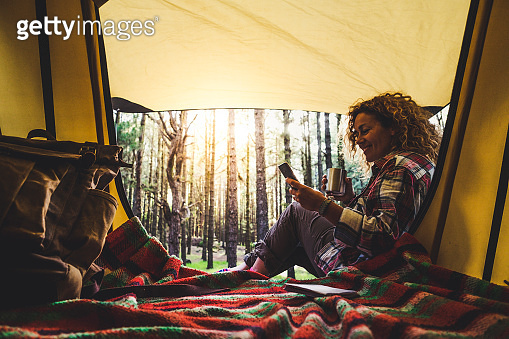 Happy free travel woman nature park camping tent lifestyle cheerful female people enjoy morning wake up outside the tent with freedom and independence - empowerment lady lifestyle