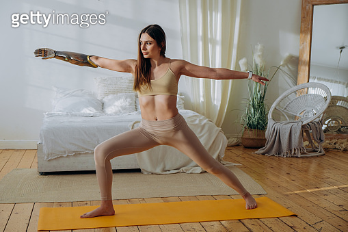 Slim woman with bionic arm stands in warrior pose in bedroom