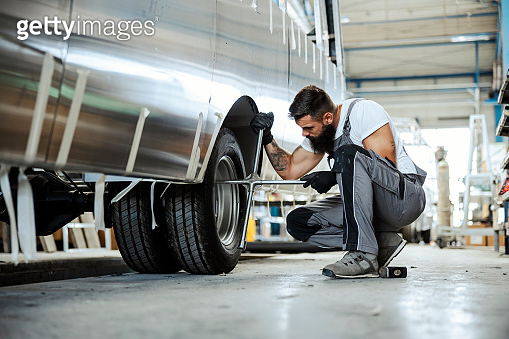 An auto-mechanic crouching next to a car wheel and replacing a tire. He is using special tools. Auto-mechanic in workshop