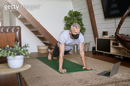 Sporty middle aged man wearing face protective mask standing in plank pose while exercising at home during self isolation, watching online workout on laptop