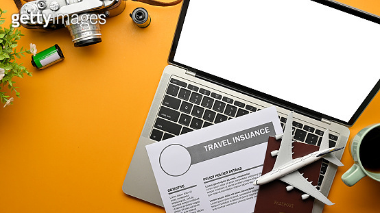 Creative flat lay photo of yellow table with laptop, travel insurance form, passport, camera, and airplane model
