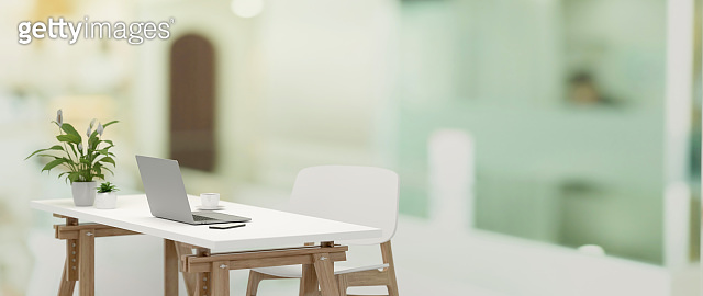 3D rendering, side view of office interior with simple office desk with laptop and office supplies in blurred home office room background