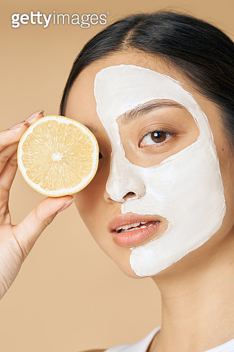 Beauty portrait of young woman with facial mask applied on half of her face holding a slice of lemon, posing isolated over beige background