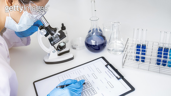 Scientist working with microscope for vaccine development in pharmaceutical research laboratory. Innovation Concept.