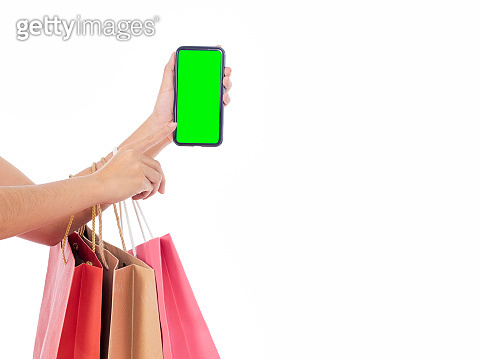 Woman holding mobile phone with blank screen and shopping bags