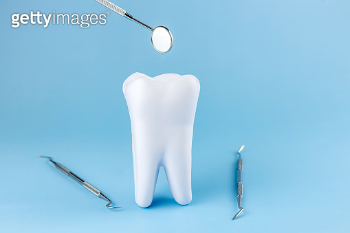 tooth model and dental instruments on a blue background