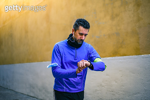 Close up of male hands using fitness app on smart watch. Man resting after jogging reading run results. Running man with smartwatch recording data about sport activity Boy checking wearable technology