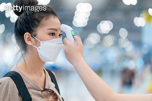 terminal staff check Asian woman body temperature with infrared forehead thermometer (thermometer gun) for virus symptom checking. Corona virus, Covid-19, quarantine or virus outbreak travel concept