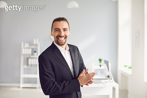 Happy businessman in formal suit standing in office