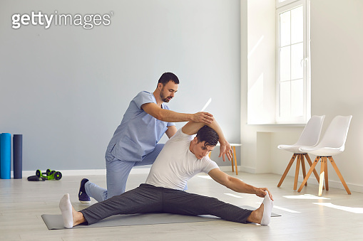 Physiotherapist helping young man do stretching exercise during rehabilitation therapy after injury