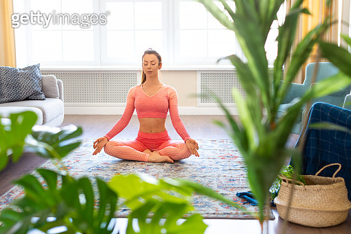 Mental health concept - woman is meditating at home. She sits in lotus position on the floor with her eyes closed and practices yoga meditation