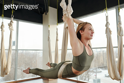 Active young blond sportswoman in grey tracksuit keeping balance on hammock