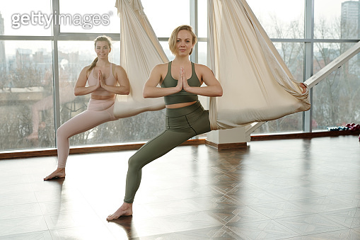 Happy young sportswomen in tracksuits using fly yoga equipment while exercising
