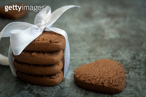 Side view of a stack of heart shaped chocolate chip cookies with a festive ribbon. Festive background