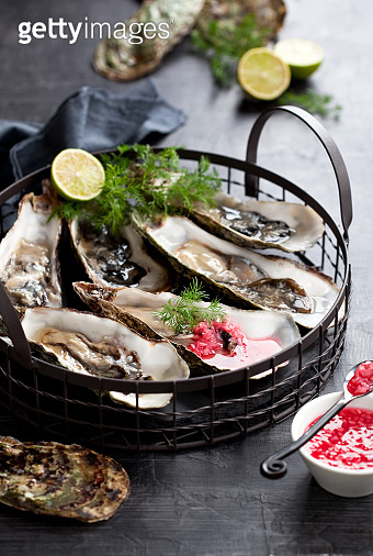 Open oysters with raspberry vinega on a plate
