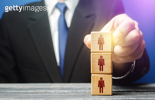 Business leader builds a people block tower. Definition of people in a hierarchical system. Meritocracy. Leadership skills, team personnel management. Company organization. Hiring, recruiting workers