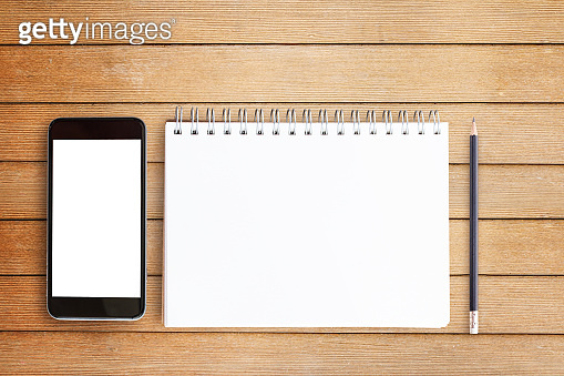Blank notepad and smart phone on wooden table background