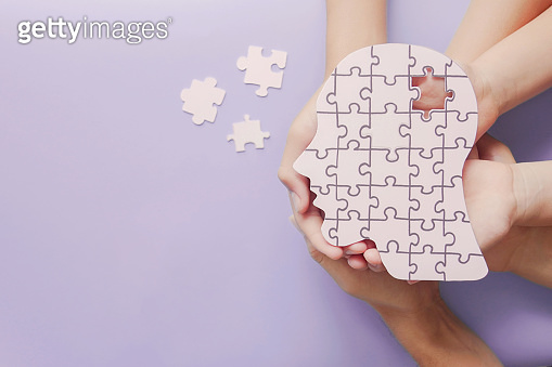 Adult and children hands holding brain with puzzle paper cutout, autism, memory loss, dementia, epilepsy and alzheimer awareness, world mental health day concept
