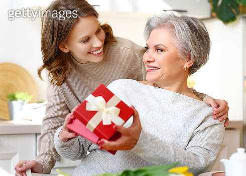 Smiling woman giving present to positive aged mother during breakfast at home