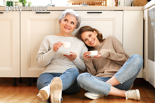 Mother and daughter drinking coffee and talking in kitchen