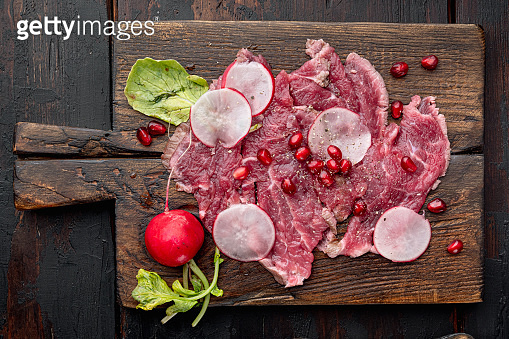 Beef Carpaccio cold appetizer, with Radish and garnet, on wooden serving board, on old dark  wooden table background, top view flat lay