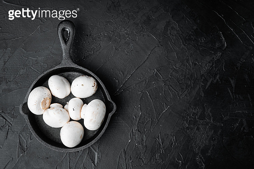 Mushroom champignon, on black stone background, top view flat lay, with copy space for text