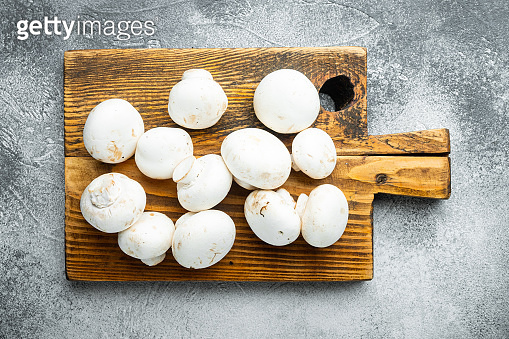 Mushroom champignon, on gray stone background, top view flat lay