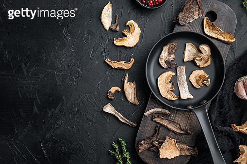 Wild organic dried porcini mushroom in cast iron frying pan, on black background, top view flat lay , with space for text  copyspace