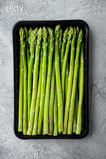 Organic raw ripe green asparagus, in plastic market  container, on gray stone background, top view flat lay