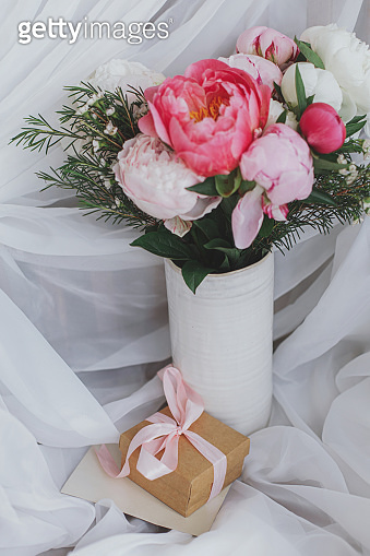 Stylish peonies bouquet, gift, greeting card on background of soft white fabric. Happy Mothers day
