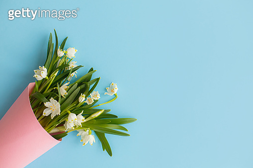 Spring flowers bouquet in pink paper cone on blue background flat lay. Happy Mothers day